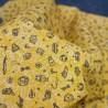 Tela de algodón color mostaza con dibujos de viajes en tonos tostados