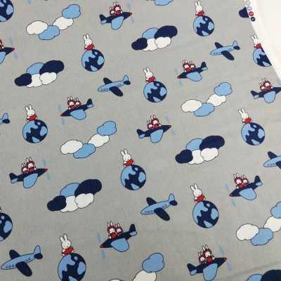 Tela de algodón gris con la conejo Miffy volando en avión