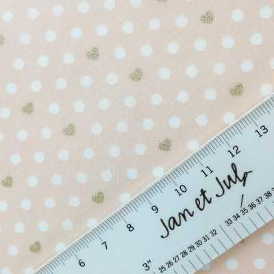 Tela de algodón americano rosa con corazones blancos y dorados