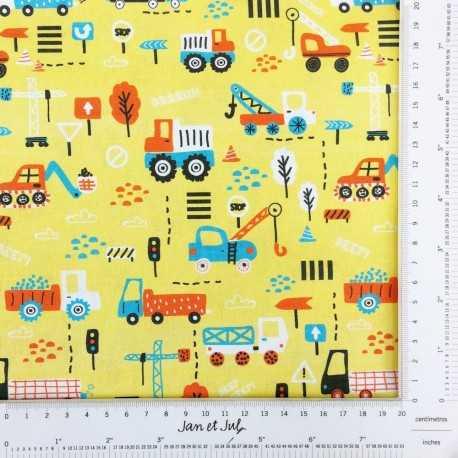 Tela amarilla de algodón con dibujos de camiones de la construcción